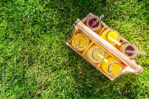 Fototapeta Assortment of lemonade and ice tea in bottles in wooden rack in the grass obraz