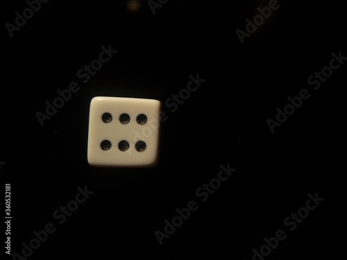 Closeup shot of white dice showing six pips isolated on a black background