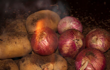Red Onions And Potatoes With Fire Flame On Foreground