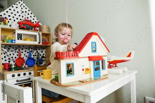 Obraz na plátne Closeup shot of a Caucasian female kid playing around her dollhouse