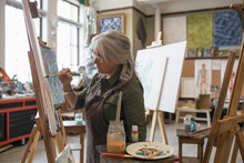Mature Woman Painting On Easel...