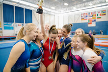 Girl Holding Trophy In Gymnasium With Friends