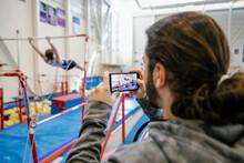 Man Filming Gymnast On Bar In ...