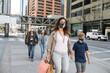 Multigenerational, family in face masks walking on city sidewalk