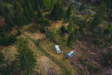 Two Old Vintage Custom Offroad Campervans Parked In The Morning Hours On The Forest Plain. Drone View Of Adventurous Night With A Car
