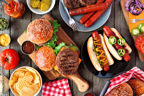 Summer BBQ food table scene with hot dog and hamburger buffet. Top view over a dark wood background.