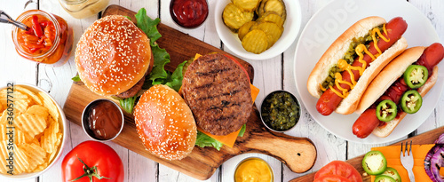 Summer BBQ food table scene with hot dog and hamburger buffet. Top down view banner over a white wood background.