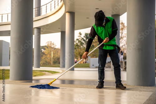 Fotografia, Obraz A  janitor man  cleaning  mopping floor in office building or walkway modern building
