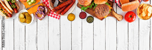 Fototapeta Summer BBQ food table scene with hot dog and hamburger buffet. Above view top border over a white wood banner background. Copy space. obraz