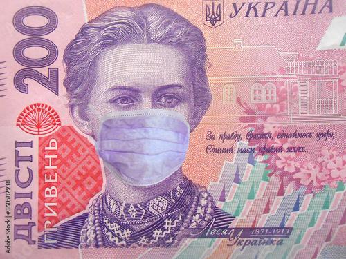Fototapeta Coronavirus COVID-19 in Ukraine. 200 ukrainian money hryvnia money bill with face mask. World economy hit by corona virus outbreak and pandemic fears. Coronavirus affects global stock market. Finance  obraz