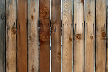 Wooden Fence A Hedge Consisting Of Sawn Flat Boards With Small Vertical Slots Between Them And Iron Nails Hammered Into Them From Which A Black Rusty Mark Is Visible