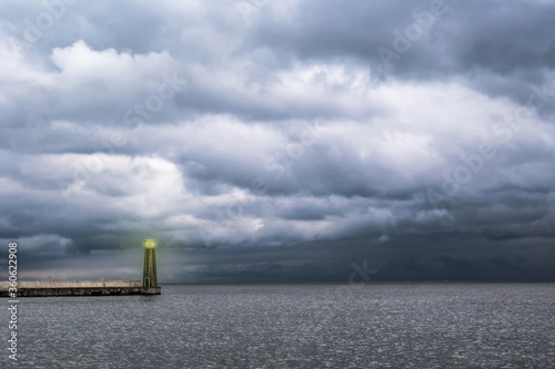 Valokuva Sea lighthouse, in the background, dramatic thunderclouds