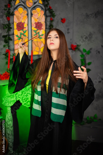Foto Young woman in a black cloak with a magic wand in her hands, standing against the backdrop of a medieval window