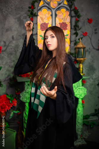 Young woman in a black cloak with a magic wand in her hands, standing against the backdrop of a medieval window Fototapete