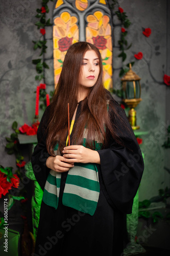 Leinwand Poster Young woman in a black cloak with a magic wand in her hands, standing against the backdrop of a medieval window