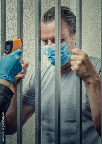 Fototapeta Measuring temperature with an infrared thermometer to a prisoner  in a mask stan