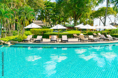 Beautiful umbrella and chair around swimming pool in hotel and resort Canvas