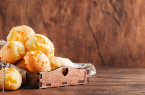 Golden Cheese buns in wooden tray, rustic kitchen table, copy space