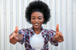 Positive emotions and people concept - portrait of attractive happy young black african american woman pointing fingers. Over grey background. Lifestyle in city.
