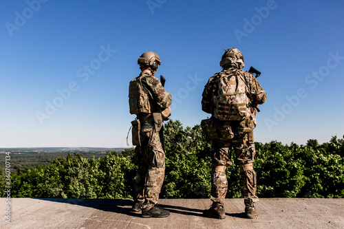Photo Two us army soldiers in camouflage standing on the roof of a building