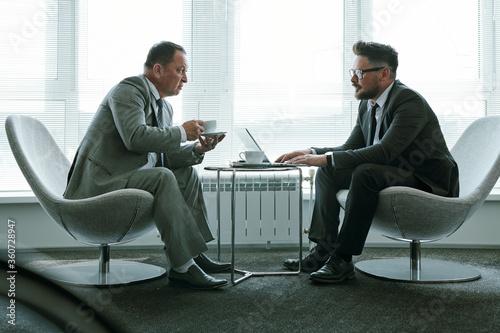 Fototapeta Two elegant businessmen in suits sitting in armchairs against office window obraz