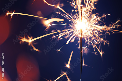Close up of burning sparkler firework with lots of hot glowing embers exploding. For New Years or 4th of July celebration. - 360763708