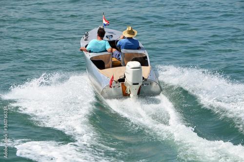Fototapeta two men in a small aluminum motorboat .