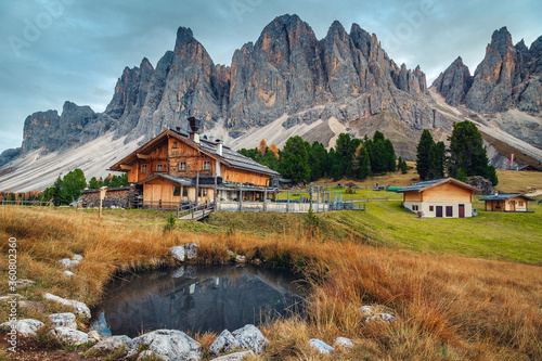 Cute alpine wooden chalets with small pond in Dolomites, Italy