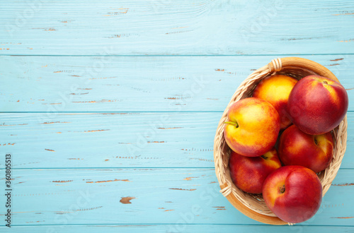 Valokuvatapetti Nectarines in a basket on blue wooden background with copy space