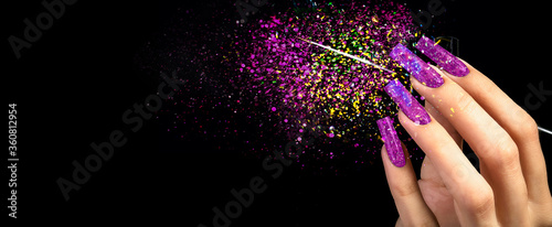 Photo Hand with bright manicure and a brush on a black background strewn with sparkles