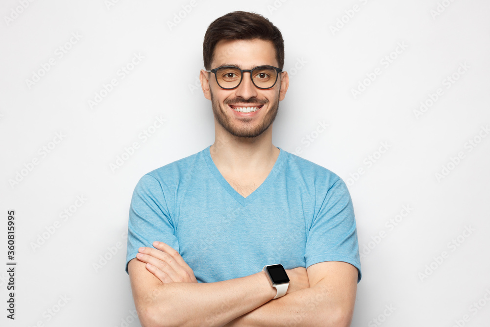 Fototapeta Portrait of confident young man standing with crossed arms, wearing glasses, dressed in casual blue t-shirt, isolated on gray background