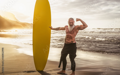 Obraz Happy fit senior having fun surfing at sunset time - Sporty bearded man training with surfboard on the beach - Elderly healthy people lifestyle and extreme sport concept - fototapety do salonu