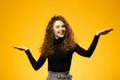 Pretty girl with curly hair on yellow background