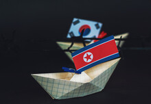 Paper Ship With Flags Of North Korea And South Korea Barbed Wire Between Them. Border Conflict Concept