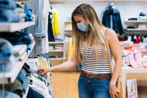 Young Woman in mask shopping at a clothing store in the coronavirus pandemic Fotobehang
