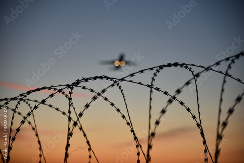 Barbed wire at airport with departing airplane at sunset Fototapet