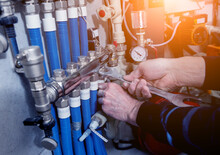 Heating Engineer Installing Modern Heating System In Boiler Room.