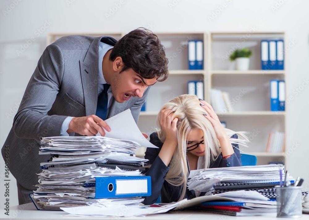 Fototapeta Angry irate boss yelling and shouting at his secretary employee