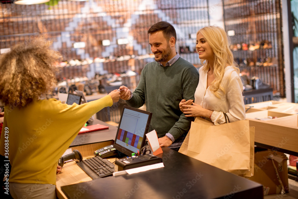 Fototapeta Man paying female sales assistant with credit card in clothes shop