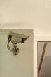 kleine graue Überwachungskamera an einer Wand unterhalb einer weißen Decke