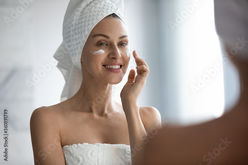Fotografía Beautiful young lady after shower look in mirror apply moisturizing facial cream