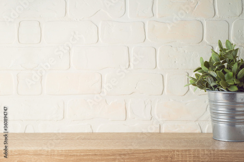 Photo Empty wooden shelf with plant over brick wall interior