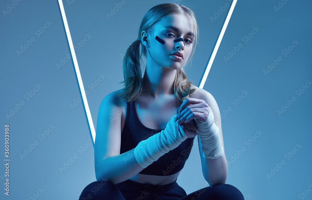Fototapeta strong beautiful girl with blonde hair, confident look, fists in protective boxing bandages