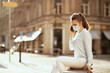 elegant woman in blue blouse talking on phone outdoors in city