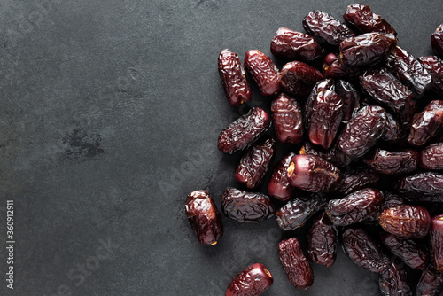 Fotomural Dried red dates on black slate background, top view copy space