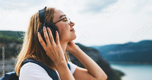 Fototapeta tourist with long hair and hipster glasses listens to her favorite music with headphones smiles and closes her eyes enjoying freedom of traveling through natural mountain landscape on vacation obraz