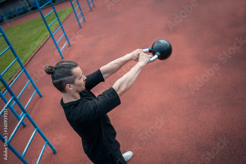 Valokuva young athlete has workout and doing sport exercises with kettlebell outdoor