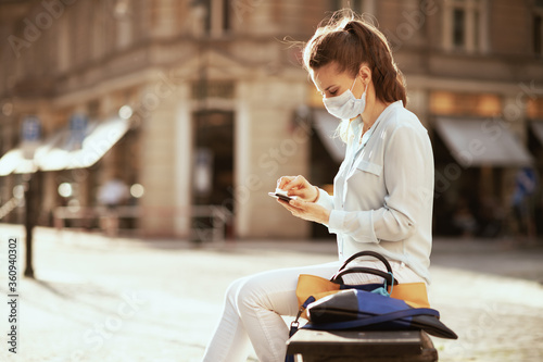 young woman wiping smartphone with sanitizer outdoors in city