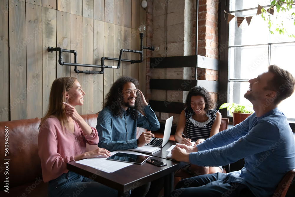Fototapeta Four friendly multi racial teammates having funny informal talk during lunch diverse devices gadgets documents lie on cafe table. Break, common project, friendship, teamwork positive activity concept