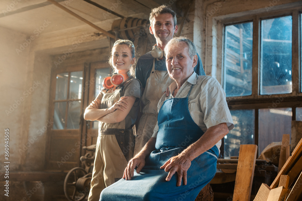 Fototapeta Generations of carpenters in their family business workshop